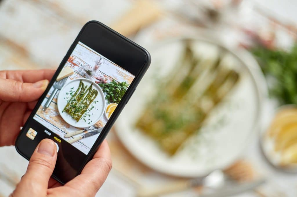 Woman taking picture of fresh prepared food with smartphone for social media. Roasted aparagus